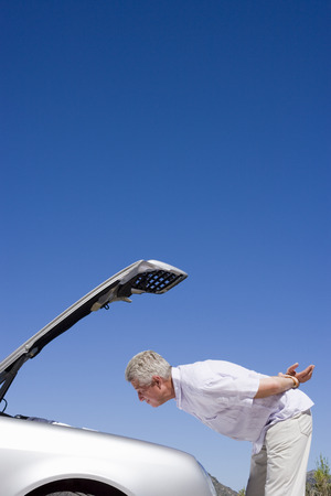 car trouble: Senior man experiencing car trouble, looking at engine, bonnet raised against clear blue sky, profile