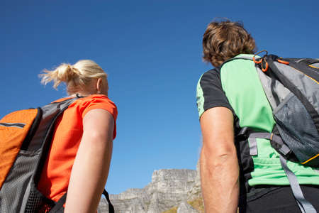 rucksacks: Rock climbing couple with rucksacks looking at rock in distance, rear view, close-up, low angle view LANG_EVOIMAGES