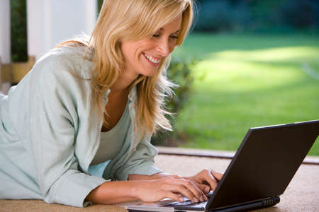 french doors: Woman lying on stomach by French doors using laptop, smiling, close-up