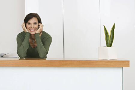 only mid adult women: Receptionist standing behind reception desk, wearing telephone headset, smiling, portrait