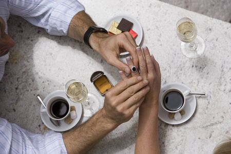 couple dining: Couple dining in restaurant, man placing engagement ring on womans finger, overhead view