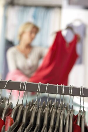 clothes rail: Mature woman shopping in clothes shop, holding red top, focus on clothes rail in foreground (tilt)