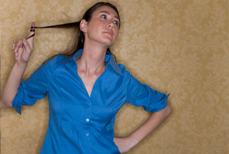 Young businesswoman with hand on hip playing with hair