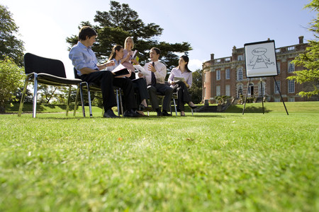 Businessmen and women with folders in training course by manor house, ground view