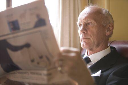 financial reward: Senior businessman in armchair reading newspaper