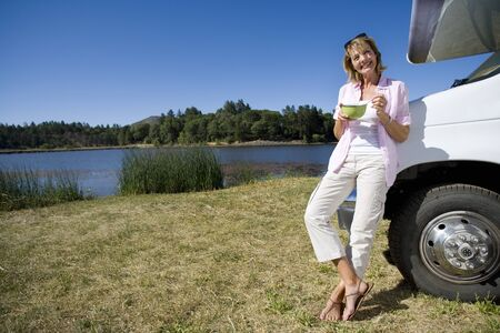 motor home: Woman with bowl by motor home and lake, smiling, portrait, low angle view LANG_EVOIMAGES