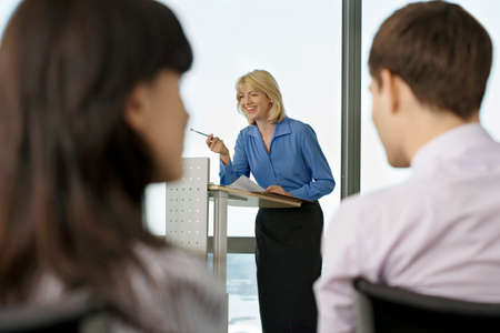 lectern: Businesswoman standing behind lectern, giving presentation to colleagues, focus on background