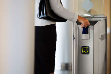differential focus: Businesswoman swiping card in entrance barrier, rear view, mid-section (differential focus)