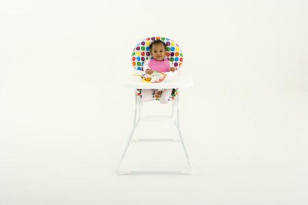 highchair: Baby girl (3-6 months) in highchair, portrait