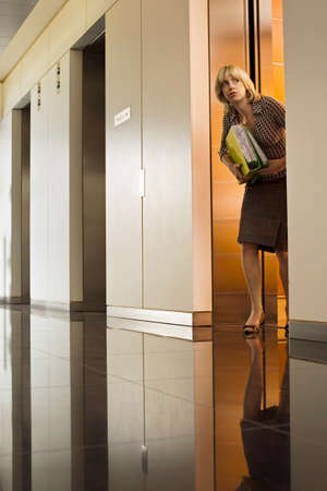 exiting: Anxious businesswoman exiting office elevator, looking nervously down corridor, surface level