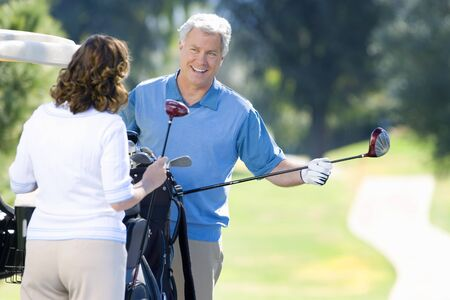 golf bag: Mature couple playing golf, man in blue tank top taking driver from golf bag, smiling LANG_EVOIMAGES