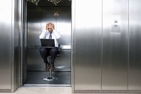 out of context: Mature businessman on stool in lift, laptop on lap, head in hands