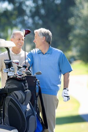 golf bag: Two mature men playing golf, man in blue tank top taking driver from golf bag, smiling