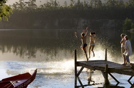 일몰 부두에 서 멀티 세대 가족, 어린이 (7-10) 호수에 점프, 측면보기 스톡 콘텐츠