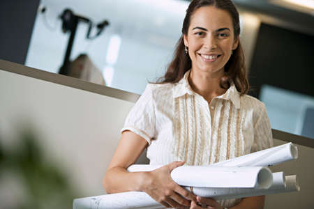 differential focus: Woman standing in office, carrying rolls of blueprints, smiling, portrait (tilt, differential focus)