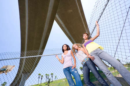 three people only: Small group of friends by fence beneath overpass, portrait, low angle view