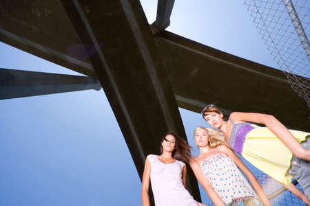 only three people: Small group of friends beneath overpass, portrait, low angle view