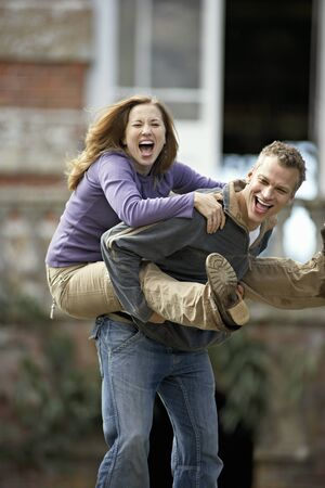 man carrying woman: Man carrying woman by piggyback, smiling, portrait
