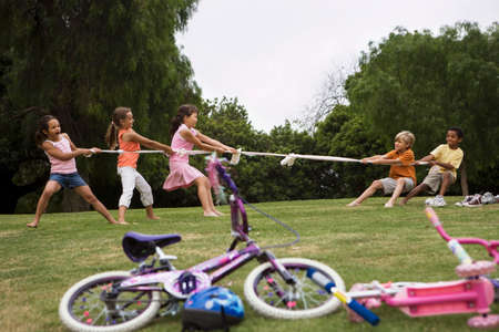level playing field: Group of children (7-9) playing tug-of-war in park near bicycles, boys versus girls, side view