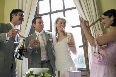 usher: Bridesmaid taking photograph of bride, groom, and usher with champagne, smiling, low angle view LANG_EVOIMAGES