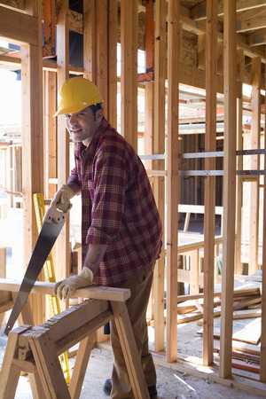 sawhorse: Builder in hardhat using saw in partially built house, portrait LANG_EVOIMAGES