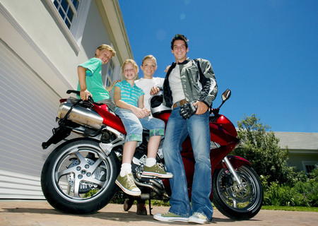 Family posing beside red motorbike on driveway, smiling, side view, portrait (surface level)