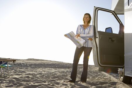 motor home: Mature woman with map by motor home on beach, smiling, low angle view (lens flare) LANG_EVOIMAGES