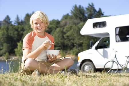 motor home: Boy (10-12) with legs crossed eating breakfast on grass, motor home in background, smiling, portrait