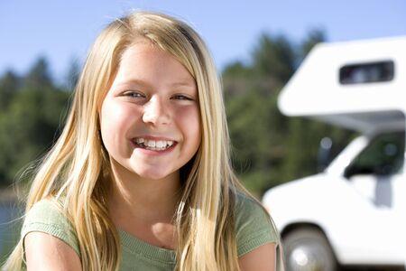 motor home: Girl (9-11) smiling, motor home in background, portrait LANG_EVOIMAGES