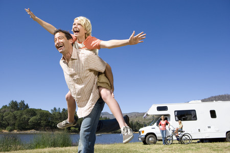 motor home: Girl (9-11) on fathers back, mother and brother (10-12) by motor home in background, low angle view LANG_EVOIMAGES