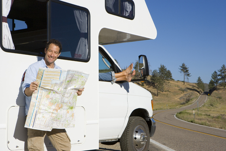 motor home: Man reading road map by woman with feet out of window of motor home