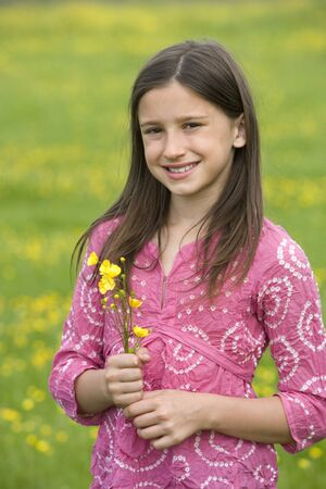 Girl (7-9) with wild flowers in field, smiling, portrait Stock Photo