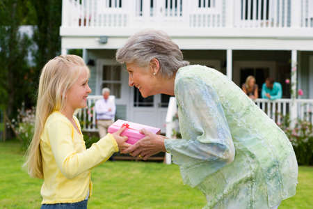 generation gap: Girl (4-6) presenting birthday gift to grandmother in summer garden, smiling, profile, family members on house veranda in background