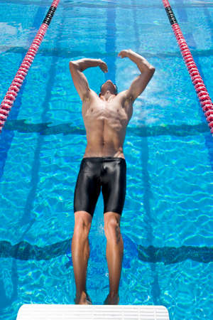 swimming pool water: Male swimmer diving into swimming pool backwards, elevated view LANG_EVOIMAGES