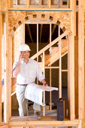 view of a wooden doorway: Architect with blueprint using mobile phone in partially built house