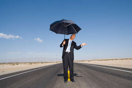 speculating: Businessman on open road in desert with umbrella, feeling for rain, low angle view LANG_EVOIMAGES