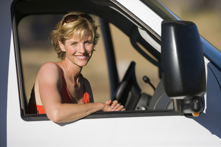 motor home: Woman in drivers seat of motor home, smiling, portrait LANG_EVOIMAGES