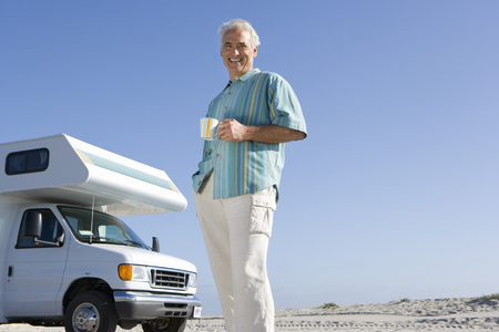 motor home: Mature man with mug by motor home on beach, smiling, portrait, low angle view LANG_EVOIMAGES