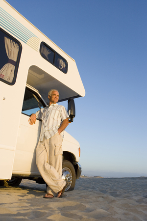 motor home: Mature man by motor home on beach, arm on door, low angle view