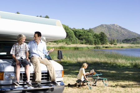 motor home: Man smiling at son (10-12) on bonnet of motor home by lake, mother reading in background LANG_EVOIMAGES