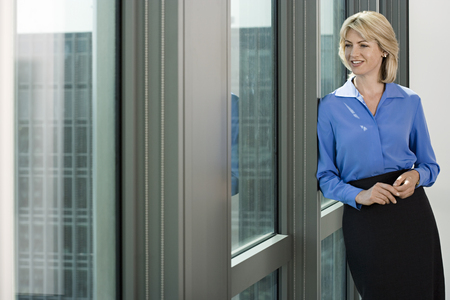 looking through frame: Businesswoman leaning against window frame in office, looking through window, smiling
