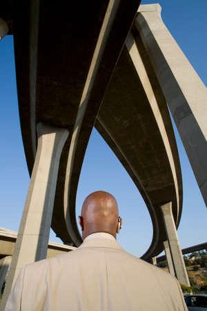beneath: Businessman beneath overpasses, rear view
