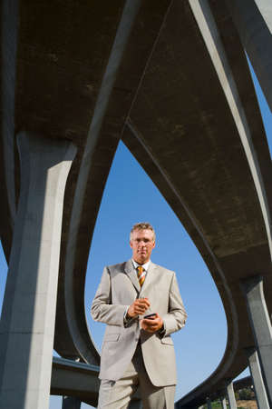 electronic organiser: Businessman using electronic organiser beneath overpasses, portrait, low angle view LANG_EVOIMAGES