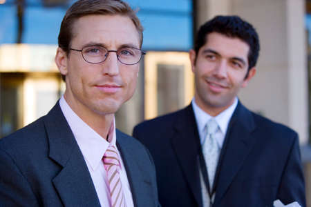 two people only: Two businessmen standing outside building, smiling, portrait (differential focus)