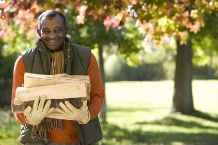 man front view: Senior man collecting firewood in autumn park, smiling, front view, portrait
