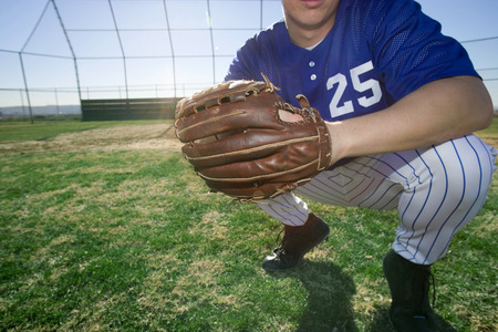 level playing field: Baseball player, wearing number '25' blue uniform and glove, crouching on pitch, close-up, low section