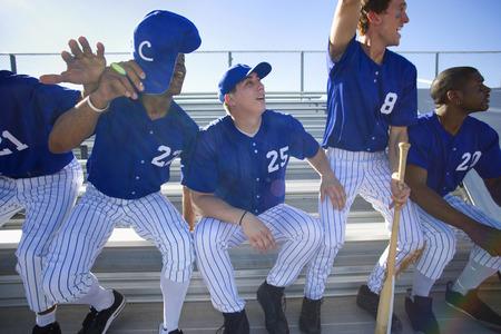 경쟁 야구 경기, 응원, 전면 뷰 (백라이트) 동안 스탠드에서 벤치에서 위로 올려 흥분된 야구 팀