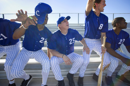 Excited baseball team jumping up from bench in stand during competitive baseball game, cheering, front view (backlit) Imagens