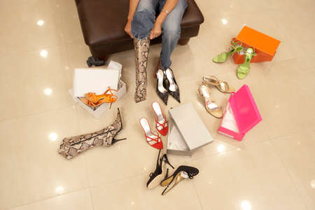 low section view: Woman trying on different pairs of high heels and boots in shoe shop, low section, elevated view LANG_EVOIMAGES