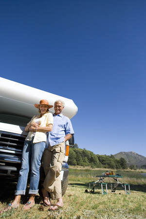 motor home: Mature couple by motor home and portable picnic table, smiling, portrait, low angle view